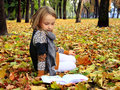 Young girl reads a book in the autumn park Royalty Free Stock Photo
