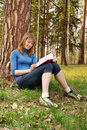 The young girl reads the book under a tree Royalty Free Stock Photo