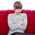 Young girl on red sofa is offended Royalty Free Stock Photo