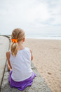 Young girl relaxing at beach sitting on wall and next to Stock Photo