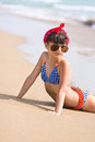Young girl in retro look with red bandana and sunglasses lays on beach Royalty Free Stock Photos