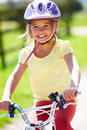 Young girl riding bike along country track in daylight wearing helmet Stock Images