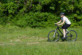 Young girl riding a bike on a field path - offroad Royalty Free Stock Photography