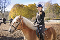 Young girl riding horse portrait of teenage outdoors on sunny autumn day Stock Photo