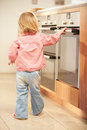 Young Girl At Risk From Hot Oven In Kitchen Stock Photo
