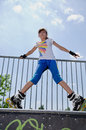 Young girl rollerskating low angle portrait of an attractive teenage standing bent forward balanced on a metal rail wearing blade Royalty Free Stock Photos