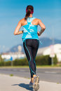 Young girl runner on the street female running woman female jogging during outdoor workout fitness model outdoors weight loss Royalty Free Stock Photography