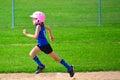 Young girl running bases softball digging hard third base Stock Image