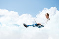 Young girl running in the clouds with a laptop place for text Stock Photography