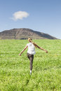 Young girl running in the field enjoying life on a summer day a beautiful grassy meadow Royalty Free Stock Photo