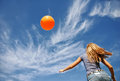 Young girl running for her orange balloon Royalty Free Stock Image