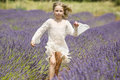 Young girl runs in purple lavender field happy little jumps of Royalty Free Stock Photos