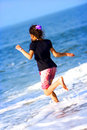 Young girl runs into waves Royalty Free Stock Images