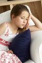 Young Girl Sat on Sofa at Home Royalty Free Stock Photos