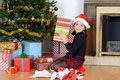 Young girl shaking christmas gift in front of tree Royalty Free Stock Photo