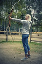 Young girl shooting with a bow blonde focuses on sport outside Stock Image