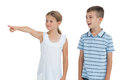Young girl showing something to her brother while posing on white background Stock Photos