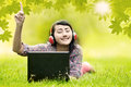 Young girl singing with laptop in park beautiful asian woman enjoys the summer day shot outdoor on the green grass Stock Image