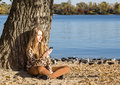 Young girl sitting on the beach and looking at mobile phone screen holding smartphone in hand Royalty Free Stock Photo