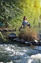 Young girl sitting by the creek resting near rapid river Royalty Free Stock Photography