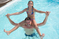 Young girl sitting on father's shoulders in swimming pool Royalty Free Stock Photo