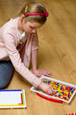 Young girl sitting floor playing colorful pins toy making picture Stock Image