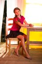 Young girl sitting near wooden table in summer inside pavilion Stock Image