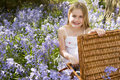 Young girl sitting outdoors with picnic basket Stock Photos