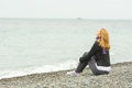 Young girl sitting on a pebble beach by sea face to the sea breeze on a cloudy day Royalty Free Stock Photo
