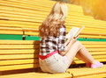 Young girl sitting reading a book on the bench in city park in summer day Stock Photography