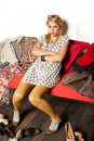 Young girl sitting on a sofa looking mad surrounded by clothes and shoes Stock Photography