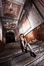 Young girl sitting on stairs at old abandoned building Royalty Free Stock Photo