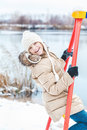 Young girl sitting on swing on bank of winter pond Royalty Free Stock Photo