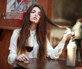 Young girl sitting at table in summer cafe with glass of wine a Royalty Free Stock Photos