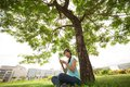 Young girl sitting under tree mp outdoors Royalty Free Stock Photography