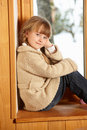 Young Girl Sitting On Window Ledge Stock Photo