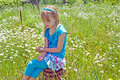 Young girl sitting on a wooden barrel caucasian in field of summer wild daisies Stock Photos