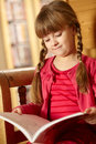 Young Girl Sitting On Wooden Seat Reading Book Stock Photography