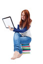 Young girl sittitting and using tablet sitting on pile of books pc Stock Image