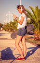 Young girl with skateboard and headphones portrait of beautiful listening music in her smartphone outdoors warm tones edition Royalty Free Stock Photos