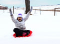 Young girl sledding a having fun on a cold winter day Royalty Free Stock Photography