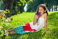 Young girl smelling flowers in her hands outdoors sitting on grass Royalty Free Stock Photo