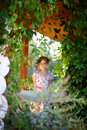 Young girl smiling on a green veranda the at the cottage the in wreath of wildflowers Royalty Free Stock Photos