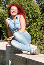 Young girl smiling red curly hair and piercing outdoor a teenage is sitting on a wall is laughing having fun she has shaved on one Stock Photos