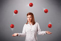 Young girl standing and juggling with red balls pretty Royalty Free Stock Images
