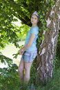 Young girl standing near birch tree in summer green park Stock Photos