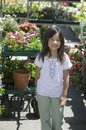 Young girl standing in plant nursery portrait Royalty Free Stock Photography