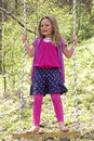 A young girl standing on a swing having fun Stock Image