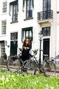 Woman girl parking vintage bicycle street old town sity black coat long curly hair enjoy sun spring glasses white house Royalty Free Stock Photo