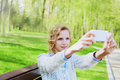 Young girl student having fun and taking selfie photo on smartphone camera outdoor in green park in sunny day teenage trand people Royalty Free Stock Photography